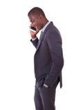 做MOBIL的一个年轻非裔美国人的商人的画象 库存照片