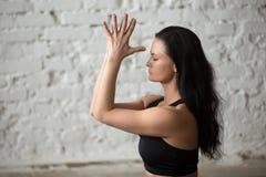 年轻做namaste,白色顶楼backgroun的信奉瑜伽者可爱的妇女 免版税库存照片