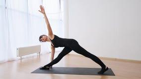 做pilates在三角姿势和在刺的年轻女人侧视图在慢动作以后 股票视频