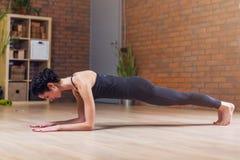 做pilates在地板上的稀薄的年轻女性信奉瑜伽者板条姿势在家行使 库存图片