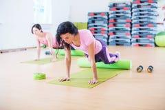 做pilates的适合的妇女行使舒展成拱形她在健身演播室 免版税库存照片