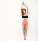 做pilates的年轻深色的妇女全长画象舒展在白色演播室背景的锻炼 库存照片