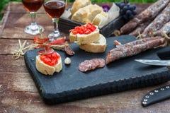 做pintxo用蕃茄和香肠,塔帕纤维布,西班牙点心集会手抓食物 免版税库存图片