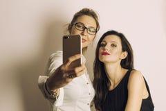 做selfie使用巧妙的电话和微笑在中立灰色背景的两名妇女 库存照片