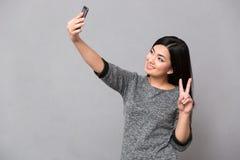 做selfie使用手机和显示和平标志的亚裔女孩 免版税库存图片