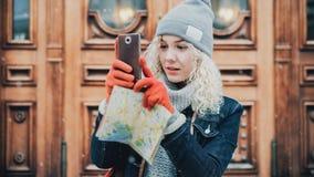 做selfie或照片的卷曲白肤金发的女孩在smartsphone 免版税图库摄影