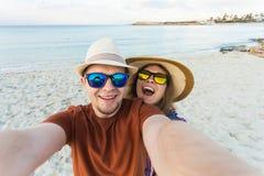 做selfie海背景,晴朗的夏天颜色,浪漫心情的愉快的旅行的夫妇 时髦的太阳镜,草帽 库存图片