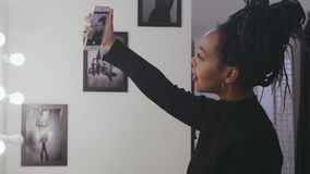 做selfie照片构成面孔前面镜子的时装模特儿在化装室 股票视频