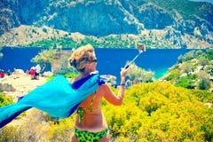 做selfie照片用selfie棍子的可爱的中间年迈的妇女在热的夏日在Kamelya海岛 免版税图库摄影