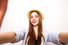 做selfie照片的一名微笑的逗人喜爱的妇女的画象由手 免版税库存照片