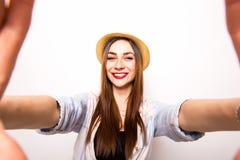 做selfie照片的一名微笑的逗人喜爱的妇女的画象由手 免版税库存图片