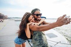 做selfie照片的一对愉快的夫妇的画象在智能手机 免版税库存图片