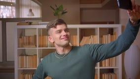 做selfie照片的年轻男生画象在是的智能手机正面和高兴的在图书馆 股票视频