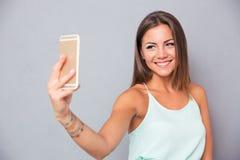 做selfie照片的微笑的女孩在智能手机 库存照片
