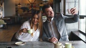 做selfie照片的微笑的女实业家和商人在咖啡馆的智能手机 影视素材