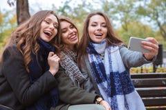做selfie照片的快乐的女朋友在智能手机 免版税图库摄影