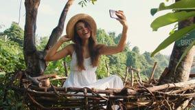 做Selfie照片的白色礼服的年轻微笑的混合的族种旅游女孩使用坐在装饰秸杆巢的手机 影视素材