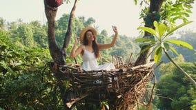 做Selfie照片的白色礼服的年轻愉快的混合的族种旅游女孩使用坐在装饰秸杆巢的手机 股票视频
