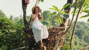 做Selfie照片的白色礼服的年轻愉快的混合的族种旅游女孩使用坐在装饰秸杆巢的手机 影视素材