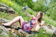 做selfie照片的美丽的白肤金发的少妇的图片在片剂有个人计算机的计算机乐趣愉快微笑在夏天户外 图库摄影
