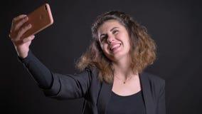 做selfie照片的超重白种人妇女特写镜头画象使用智能手机在黑背景 股票视频
