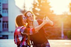 做selfie照片的画象愉快的两个微笑的女孩的在智能手机 都市的背景 在的晚上日落 免版税库存照片