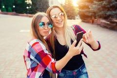 做selfie照片的画象愉快的两个微笑的女孩的在智能手机 都市的背景 在的晚上日落 库存照片