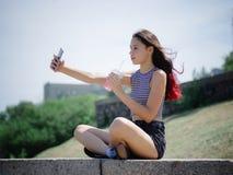 做selfie画象的一个相当十几岁的女孩在公园背景 户外,步行概念 复制空间 免版税库存图片