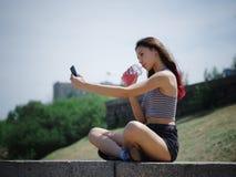 做selfie画象的一个相当十几岁的女孩在公园背景 户外,步行概念 复制空间 库存照片