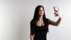 做selfie的一名快乐的年轻俏丽的妇女的全长画象使用在白色背景的手机 免版税库存照片