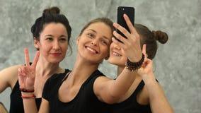 做selfie的三个少妇在锻炼以后在瑜伽类 库存照片