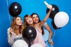 做selfie的三个美丽的女孩在蓝色背景的党 图库摄影