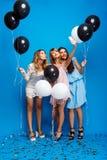 做selfie的三个美丽的女孩在蓝色背景的党 库存图片