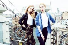 做selfie的两个凉快的白肤金发的真正的女朋友在屋顶上面, lif 库存照片