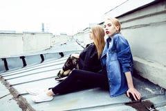 做selfie的两个凉快的白肤金发的真正的女朋友在屋顶上面, lif 免版税库存照片