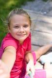 做selfie的可爱的小女孩在操场户外 库存图片