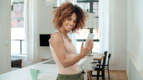 做selfie的可爱的年轻黑人妇女在厨房里 图库摄影