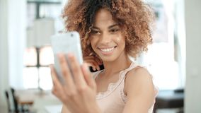 做selfie的可爱的年轻黑人妇女在厨房里 免版税库存图片