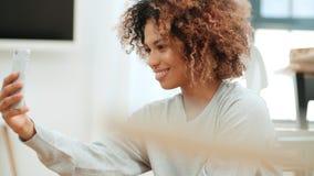 做selfie的可爱的年轻黑人妇女在厨房里 免版税图库摄影