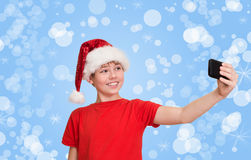 做selfie的圣诞老人帽子的滑稽的青春期前的男孩在圣诞节holida 图库摄影