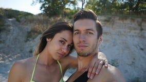 年轻做selfie的夫妇人和女孩在海滩的夏天在日落 股票录像