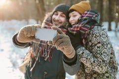 做selfie的夫妇在冬天森林里 免版税图库摄影