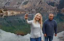 做selfie的夫妇在湖 免版税库存照片