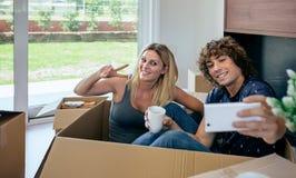 做selfie的夫妇坐在移动的箱子里面 免版税库存图片