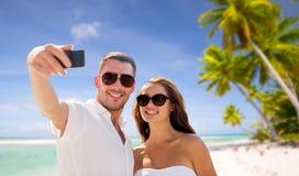 做selfie的夫妇由在海滩的智能手机 免版税图库摄影