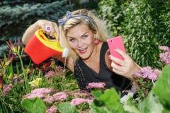 做selfie的妇女,当从事园艺-智能手机摄影时 免版税库存照片