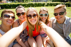 做selfie的小组微笑的朋友在公园 库存照片