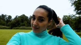 做selfie的年轻可爱的妇女在巧妙的电话在赛跑期间在绿色公园 股票录像