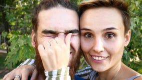 做selfie的年轻夫妇 有胡子的一个人和有一个短发的一个女孩切断自己并且无所事事在 影视素材