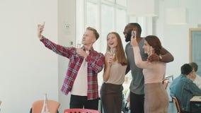 做selfie的微笑的人民在coworking的空间 摆在照相机的快乐的队 股票录像